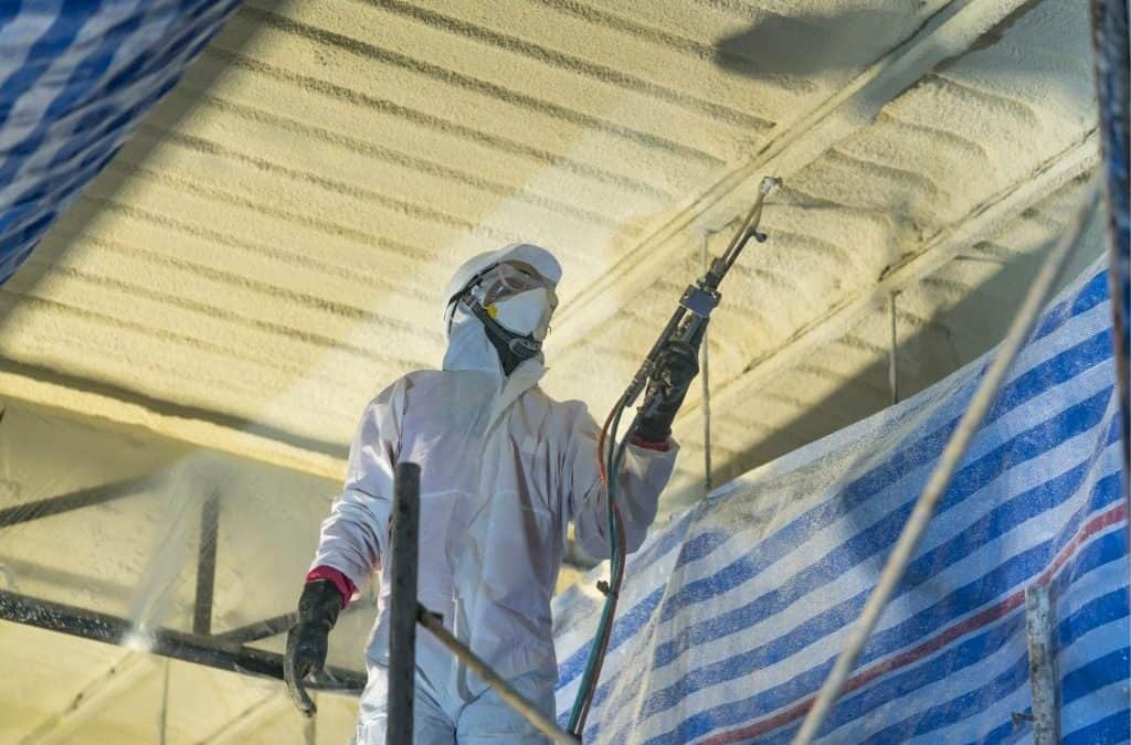 Worker spraying polyurethane foam likely containing isocyanates onto interior industrial facility surface, a target for isocyanates sampling
